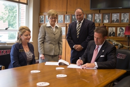 EKU President Michael Benson, right, signs the agreement.  Others, from left, ar